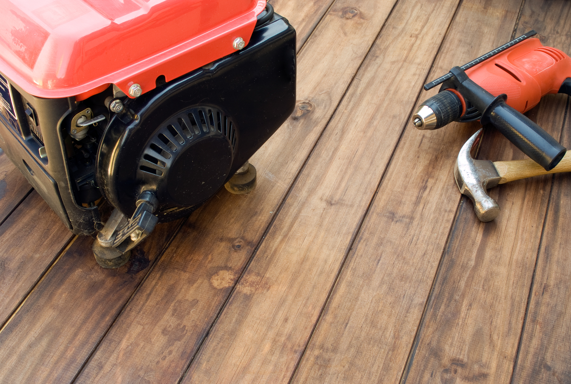 Home portable generator, drill, and hammer on wooden table